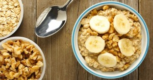 Banana walnut overnight oatmeal in a bowl on wood table, overhead view