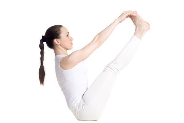 Sporty beautiful young woman in white sportswear doing exercises for legs and abs, sitting in Ubhaya Padangusthasana asana, Both Big Toe pose, studio full length isolated shot, side view