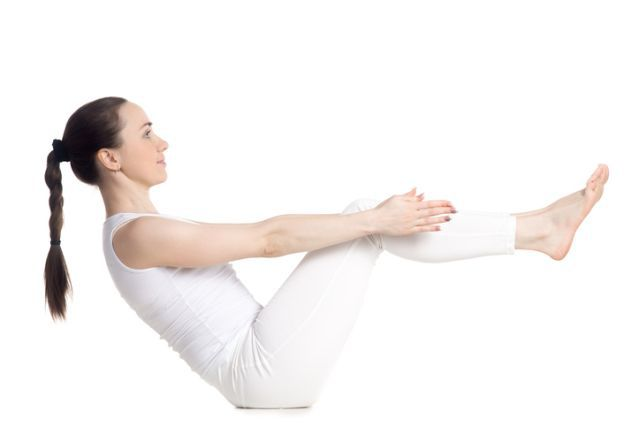 Sporty beautiful smiling young woman in white sportswear doing exercises for back, legs and abs, sitting in Paripurna navasana, boat pose variation, studio full length isolated shot, side view